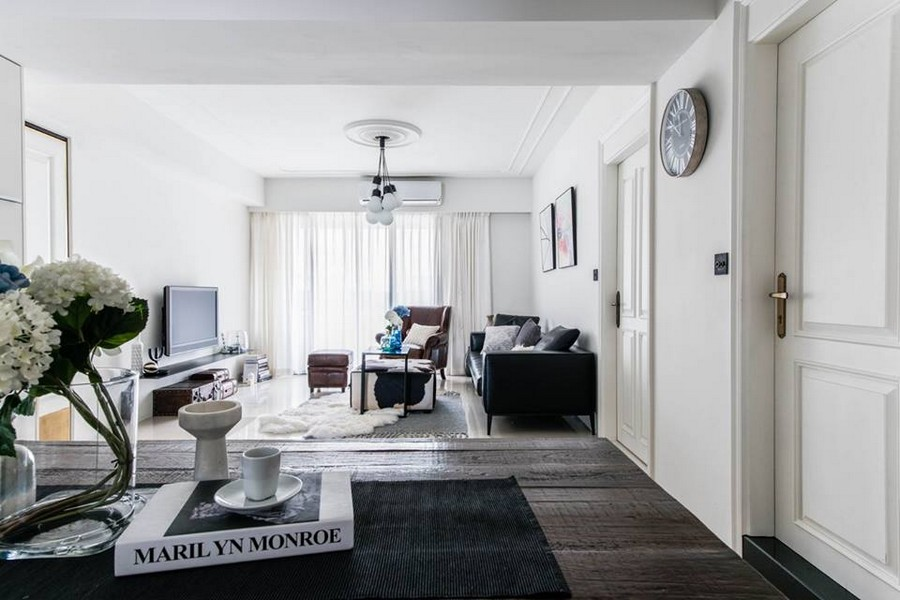 1-1-eclectic-Scandinavian-and-French-style-interior-open-concept-living-dining-room-white-walls-doors-black-furniture-sofa-coffee-tables-cornices-ceiling-medallion
