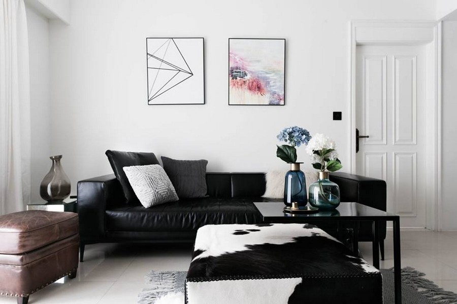 1-2-eclectic-Scandinavian-and-French-style-interior-lounge-living-room-black-leather-sofa-throw-pillows-coffee-tables-white-walls-brown-ottoman-wall-artwork-painting-padded-stool-leather