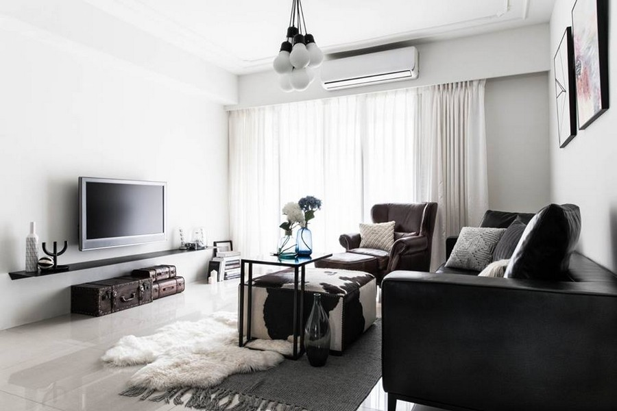 1-3-eclectic-Scandinavian-and-French-style-interior-lounge-living-room-wall-mounted-TV-rack-vintage-suitcases-on-the-floor-white-walls-black-sofa-coffee-tables-group-of-lamps-bulbs-cornices