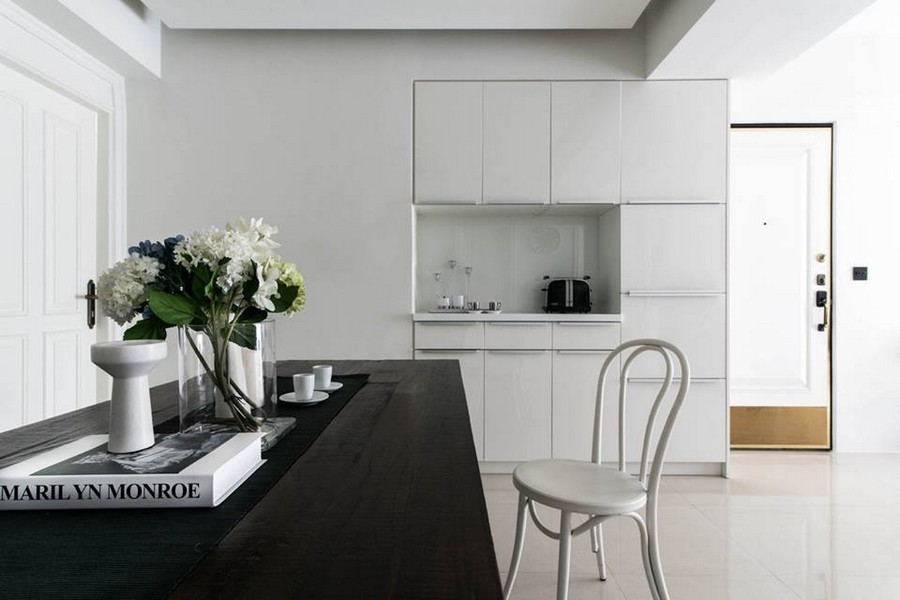 2-1-eclectic-Scandinavian-and-French-style-interior-dining-room-small-kitchen-white-cabinets-minimalistic-dark-brown-wooden-table-chairs-doors