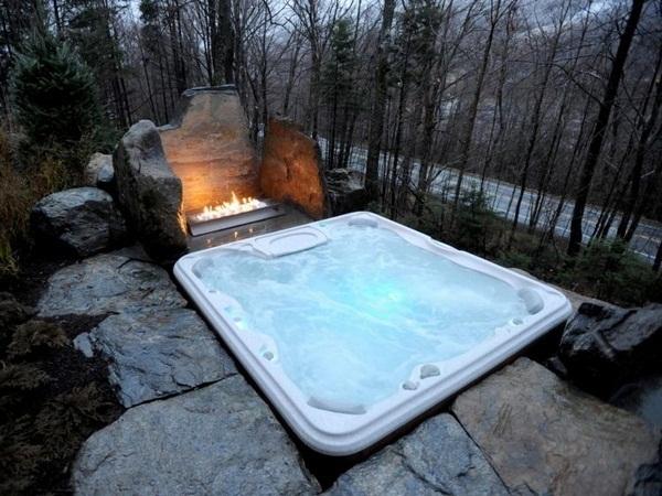 Whirlpool garden outdoor small spa built around ground rocks