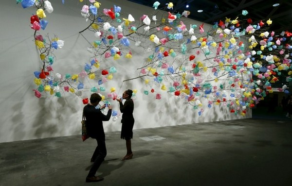 Visitors take a picture in front of the installation &quotPlastic Tree&quot by Cameroonian artist Tayou at the Art Unlimited exhibition at the Art Basel fair in Basel