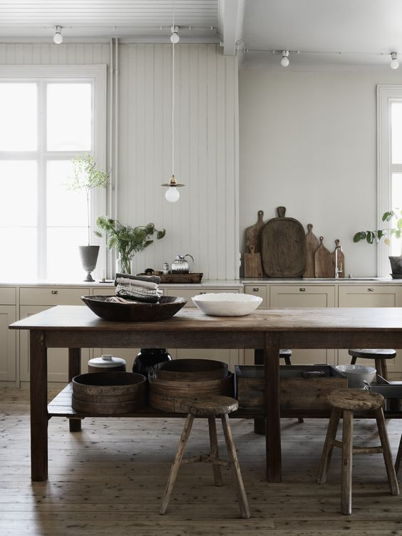 kitchen with big old wooden table and raw wooden stools