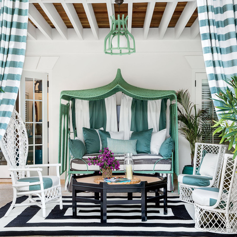 downstairs patio, teal and white striped curtains, 3 white chairs, black coffee table with purple flowers and a candle on a black and white rug, teal light fixture above, teal and while cabana with teal and white striped pillows,