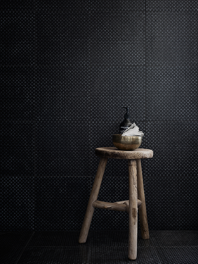 bathroom with black textured tiles. raw wooden stool.