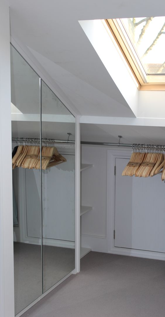 closet with mirror doors and clothes hangers