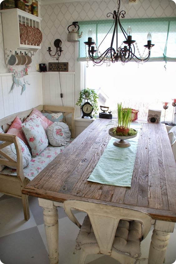 reclaimed wood table with a delicate table runner and a shabby bench with floral textiles