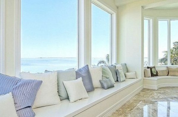 comfortable sofa with pillow next to the large windows in the house panorama