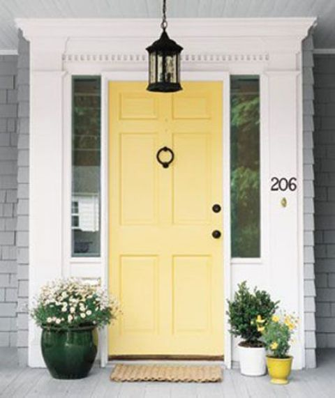 sunny yellow modern front door with yellow pots next to it