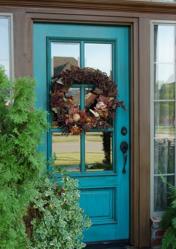 teal glass front door with a wreath fro decor and privacy