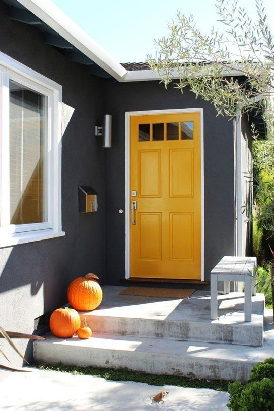 yellow front door in a black painted house