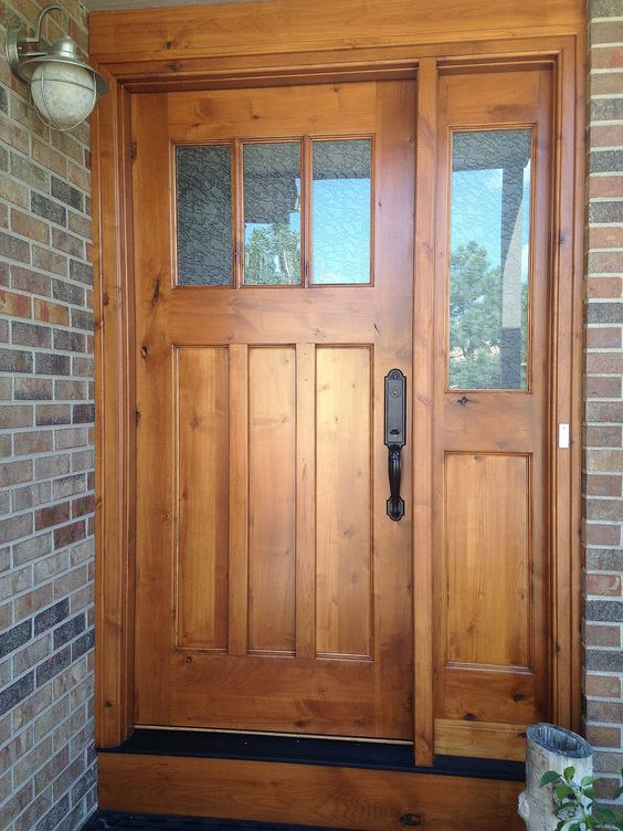 stained tan wooden door with one sidelight