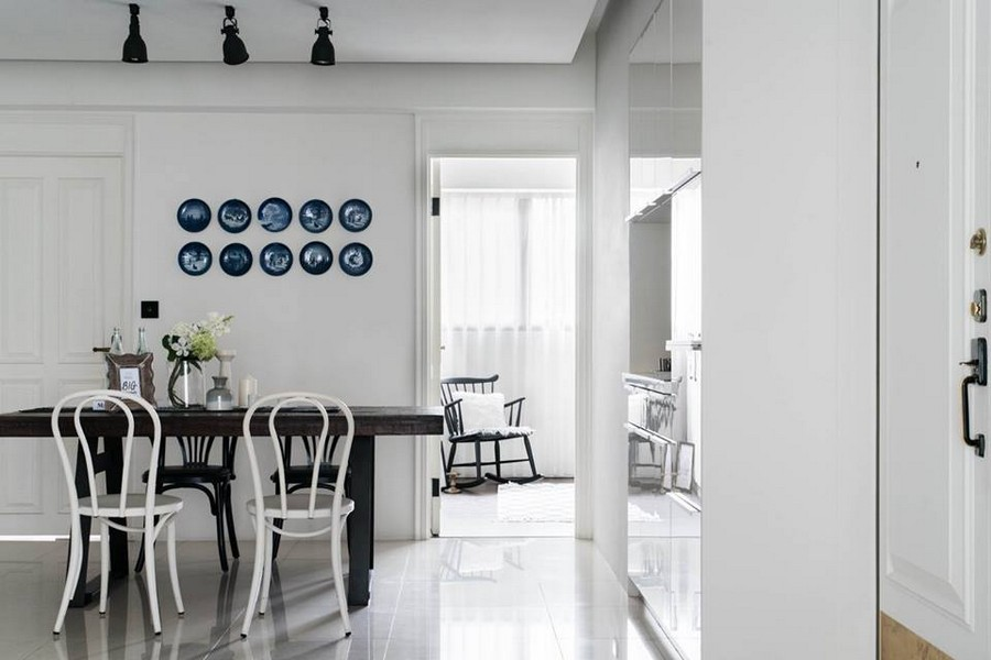 2-2-eclectic-Scandinavian-and-French-style-interior-open-concept-dining-room-kitchen-white-walls-dark-brown-table-mismatched-chairs-blue-decorative-wall-plates-track-lights-bedroom-exit-door