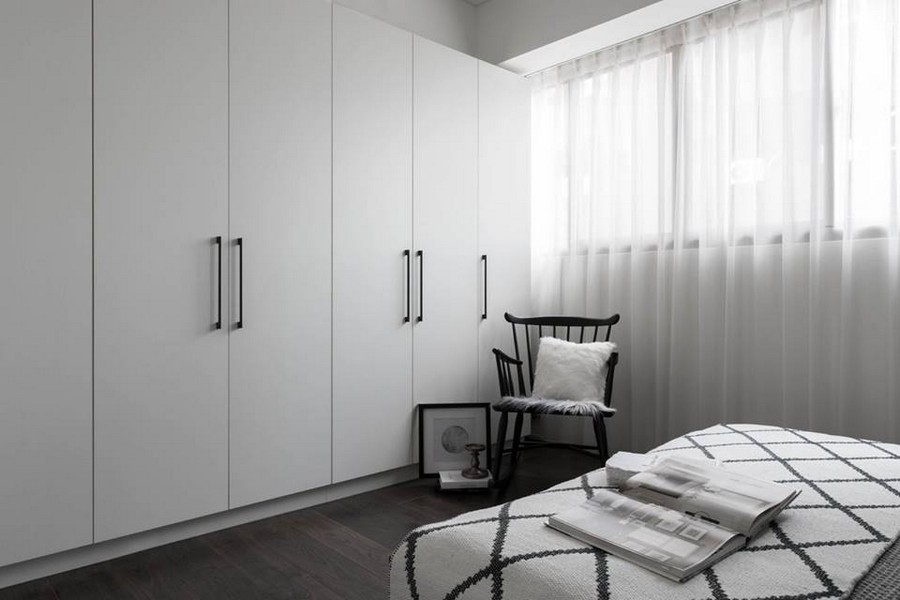 3-3-eclectic-Scandinavian-and-French-style-interior-bedroom-black-white-gray-geometrical-cover-bedspread-rocking-chair-throw-pillows-curtains-wall-to-wall-closet-wardrobe