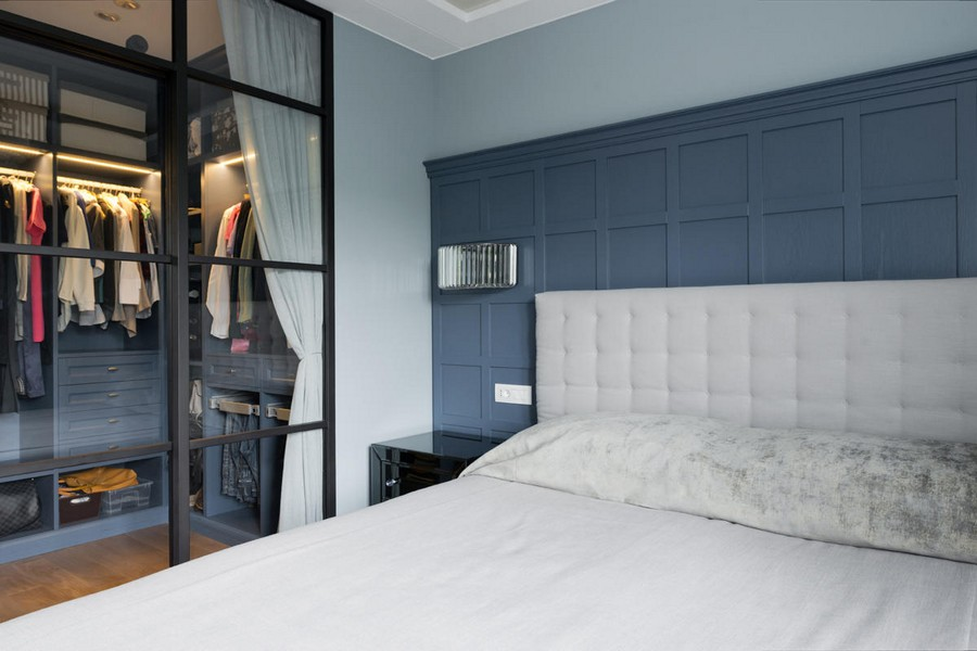 6-1-American-style-interior-blue-wooden-wall-panelling-bedroom-upholstered-bed-white-headboard-transparent-glass-wall-metal-frame-walk-in-closet-entrance-sconces