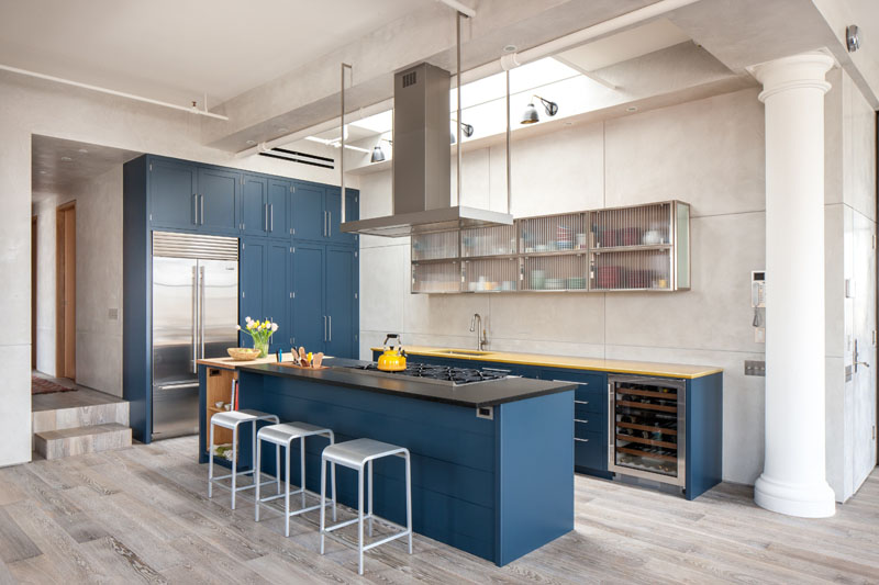 The rich blue kitchen cabinets and stainless steel hardware with the yellow accent details make this kitchen feel sophisticated yet playful.