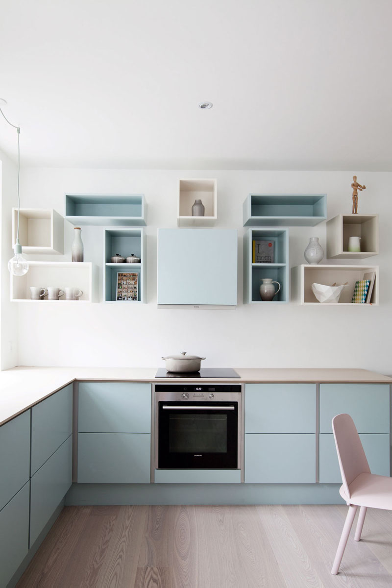 A soft blue has been used on the lower cabinets, as well as on and inside of some of the upper open box shelves to create a bright, welcoming kitchen.