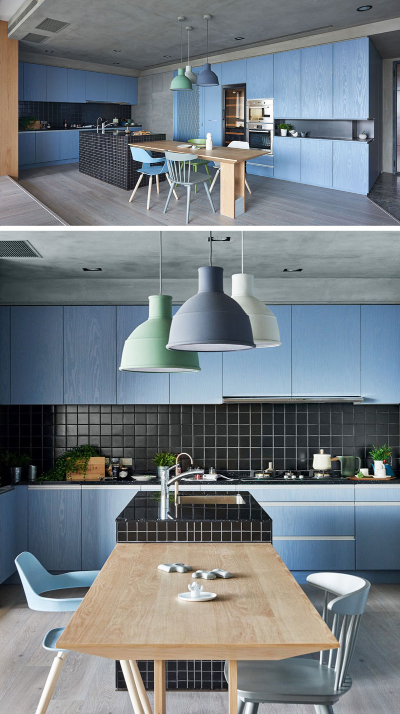 The lack of hardware combined with the grey wood floor and concrete ceiling really brighten and intensify the blue kitchen cabinets.