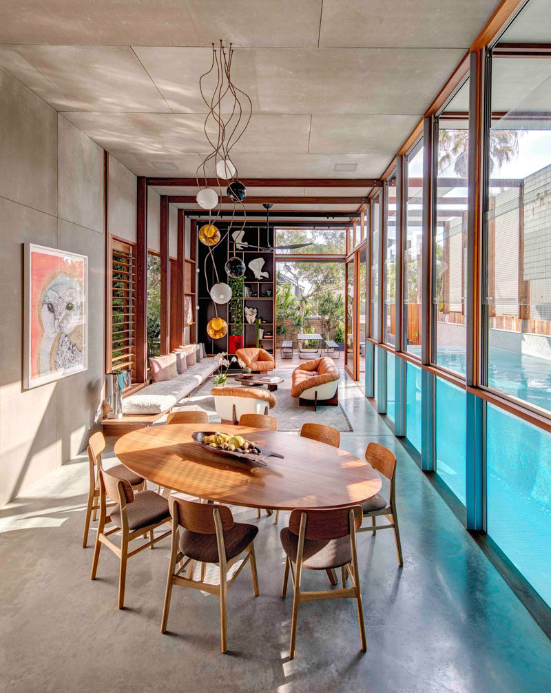 Sculptural lighting hangs from the ceiling above the oval dining set featured in this modern house. The wood furniture compliments the wood window frames and louvers.