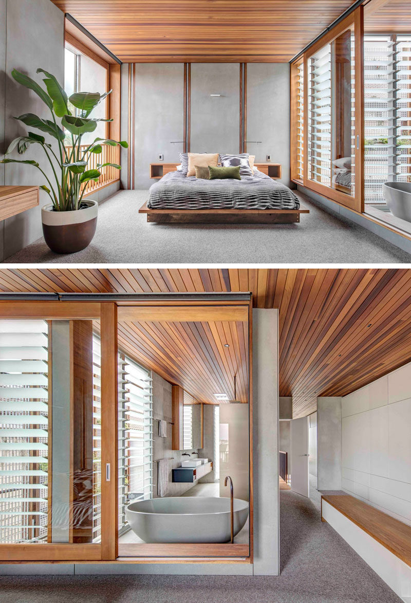 This master bedroom, minimal in its design, has large walls of windows that open to let a cross breeze through. The wood ceiling continues from the bedroom through to the ensuite bathroom that's separated with a large sliding glass window.