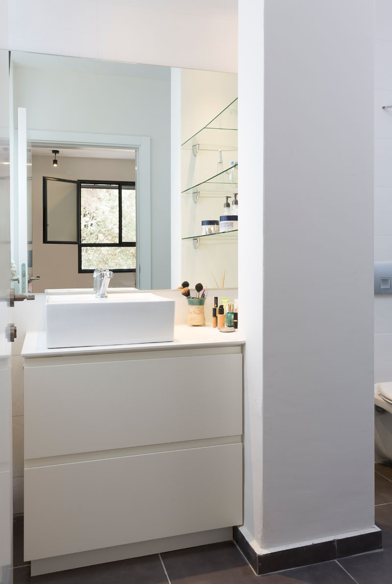 In this small modern bathroom, a white countertop sink with pull-out drawers is placed opposite the window. Accessible glass shelving has been placed to the right of the sink, separating the vanity from the toilet.