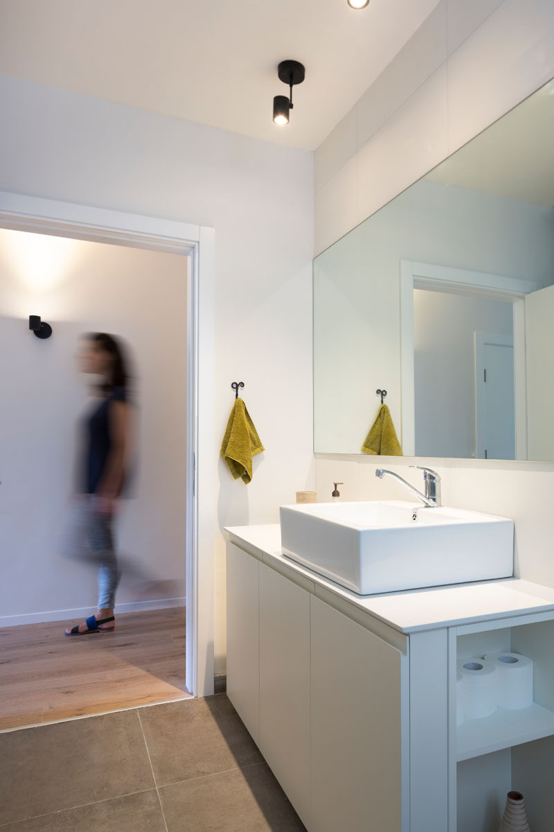 In this modern bathroom, a large mirror hangs above a square white sink and long vanity, while cabinetry below it has open shelves on one side.