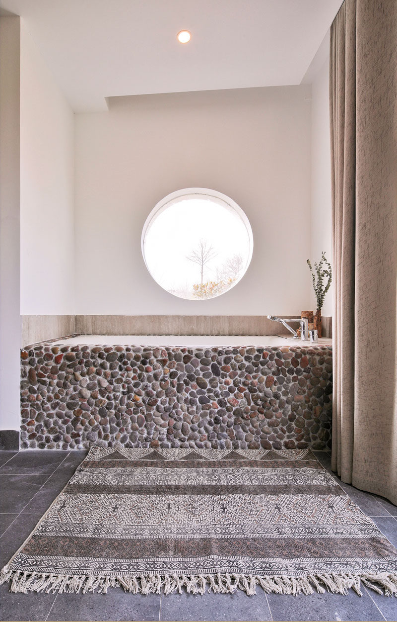 This modern bathroom features a built-in bathtub with a pebble front, that sits below a circular window. #BuiltInBathtub #BathroomDesign #Natural #Windows