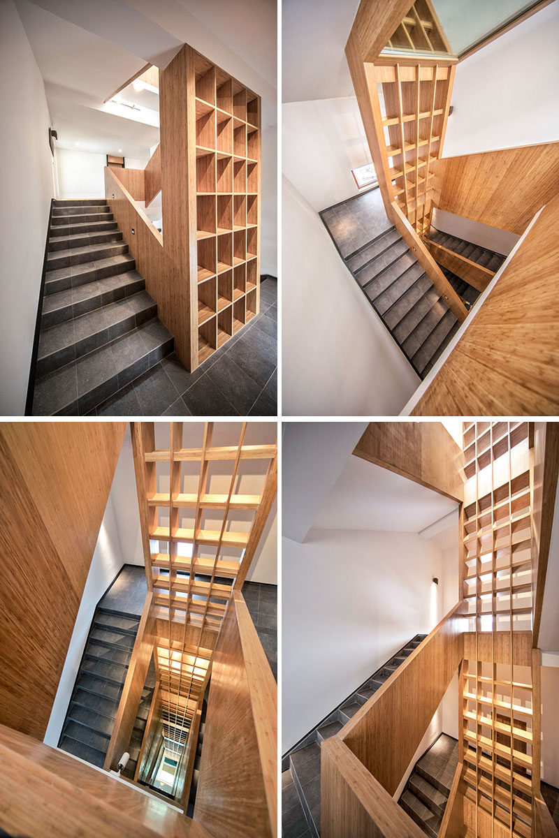 A staircase with stone tile, wood handrails and a large multi-floor wood bookshelf, connects the various levels of the hotel. #Stairs #Staircase #WoodBookshelf