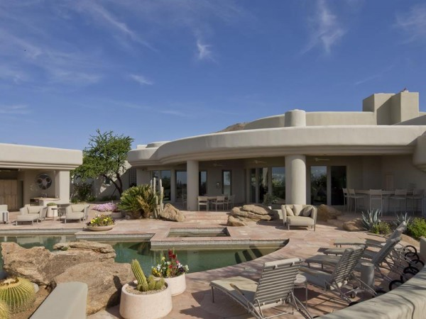 The flat roof and pale beige adobe-style exterior is firmly situated in the classic Southwest style.