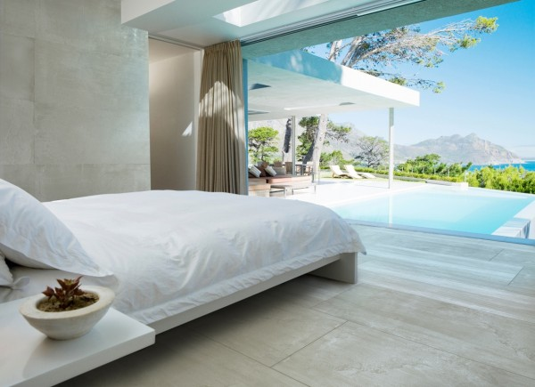 The cozy white linens and simple bed frame all but melt away in view of the spectacular pool and far away mountains.